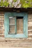 Janela de madeira de turquesa de uma casa de madeira, com o telhado enchido com o musgo fotografia de stock