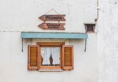 Janela de madeira pequena com as duas setas que apontam à igreja e ao t Fotografia de Stock