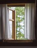 Janela de madeira rústica com as cortinas brancas com vista em defocused Imagens de Stock Royalty Free