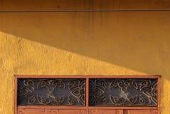 Janela de madeira tailandesa retro alaranjada e aço curvado com a parede amarela sob a luz solar da noite foto de stock