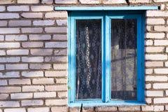 Janela de madeira velha azul na casa de uma vila branca do tijolo Imagens de Stock Royalty Free
