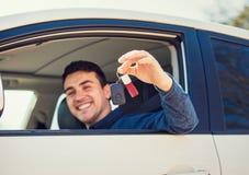 Janela de sorriso positiva das chaves do carro da exibi??o do motorista do homem novo para fora imagens de stock