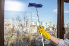 Janela de vidro de limpeza da mão As mãos fêmeas em luvas amarelas brilhantes lavam as janelas fotografia de stock