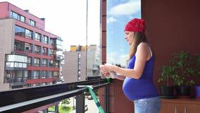 Janela de vidro de limpeza da mulher gravida feliz com a loggia de pano de pano em casa filme