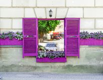 Janela do café com obturadores e as flores violetas na soleira foto de stock royalty free