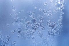 Janela do inverno com teste padrão gelado dos flocos de neve e de gotas congeladas da água foto de stock