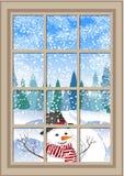 Janela do Natal do inverno com uma vista do cartão de Natal nevado da floresta janela do inverno com a paisagem e o boneco de nev Imagens de Stock Royalty Free