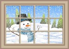 Janela do Natal do inverno com uma vista do cartão de Natal nevado da floresta janela do inverno com a paisagem e o boneco de nev Imagem de Stock Royalty Free