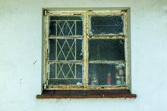 Janela e vidro negligenciados oxidados na parede azul suja Fotos de Stock