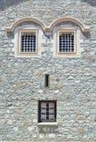 Janela em uma parede de pedra da casa Devido ao lugar das janelas, fachada olha como um rosto humano fotos de stock royalty free