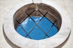 Janela medieval redonda com opinião de céu azul das barras - fundo abstrato do conceito - dentro fora conceito - janela redonda c fotografia de stock