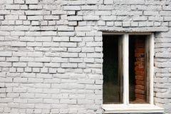 A janela na frente de uma parede de tijolo branca Fotografia de Stock Royalty Free