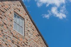 Janela na parede de tijolo marrom e no telhado de madeira no estilo do vintage com fundo do céu azul Fotos de Stock