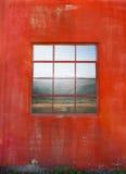 Janela na parede vermelha suja Fotos de Stock