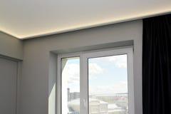 Janela na sala de visitas com a iluminação escondida do diodo emissor de luz de um teto do estiramento fotografia de stock royalty free
