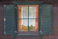 Janela no estilo antigo com obturadores abertos e as cortinas a céu aberto para dentro imagem de stock