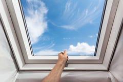 Janela nova aberta da mansarda da claraboia do homem em uma sala do sótão contra o céu azul Imagens de Stock Royalty Free