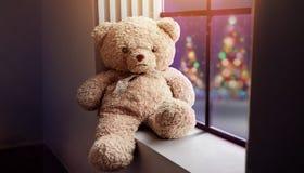 Janela próxima só de Teddy Bear Sitting na casa no Ni do Natal foto de stock