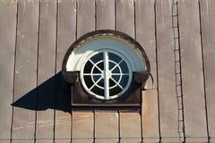 A janela redonda do sótão em um metal cobriu o telhado foto de stock royalty free