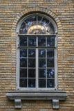 Janela retro na casa do tijolo com borda de mármore e pintura rachada, com exibição iluminada do candelabro através do vitral arq imagem de stock royalty free