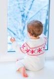 Janela seguinte do bebê ao jardim nevado no dia de Natal Fotos de Stock