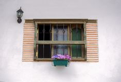 Janela tradicional com uma planta e uma luz velha fotografia de stock