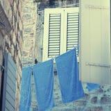 Janela velha com obturadores e linho de lavagem azul Foto de Stock