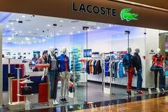 Janelas da loja de Lacoste em um shopping Moscou Foto de Stock