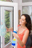 Janelas de lavagem da mulher moreno com pulverizador fotografia de stock