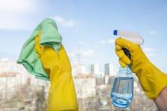 Janelas de limpeza com pano e o líquido de limpeza especiais foto de stock royalty free
