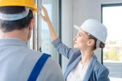 Janelas de verificação do arquiteto e do trabalhador da construção no local imagens de stock