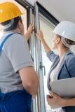 Janelas de verificação do arquiteto e do trabalhador da construção no local fotos de stock
