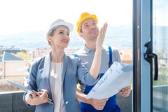 Janelas de verificação do arquiteto e do trabalhador da construção no local fotografia de stock