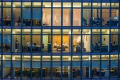 Janelas do escritório do arranha-céus e trabalhador de escritório na noite foto de stock royalty free