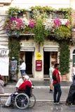 Janelas italianas do balcão completamente das plantas e das flores foto de stock
