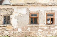 Janelas quebradas da casa abandonada velha com emplastro danificado e fundação má fotografia de stock