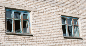 Janelas quebradas em uma construção de tijolo Imagens de Stock Royalty Free