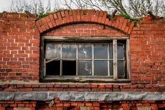 Janelas quebradas em uma construção velha com tijolos quebrados imagem de stock