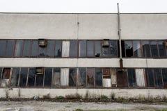 Janelas quebradas em uma fábrica abandonada velha Foto de Stock
