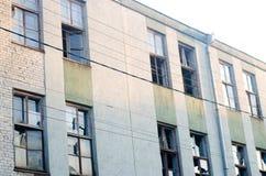Janelas quebradas na fábrica, construção abandonada Imagens de Stock