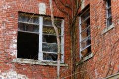Janelas quebradas velhas na construção abandonada do asilo do tijolo foto de stock royalty free