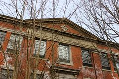 Janelas quebradas velhas na construção abandonada do asilo do tijolo fotografia de stock royalty free