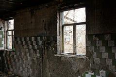 Janelas quebradas velhas na sala suja carbonizada de uma casa abandonada foto de stock royalty free