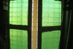 Janelas verdes do vidro velho do vintage com pa floral ou geométrico fotografia de stock royalty free
