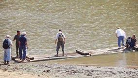 Jangada de madeira caucasiano da placa de turistas grande no banco do lago video estoque