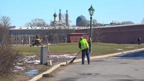 Janitor καθαρίζει το πεζοδρόμιο, ηλιόλουστη ημέρα άνοιξη γέφυρα okhtinsky Πετρούπολη Ρωσία Άγιος απόθεμα βίντεο