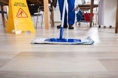 Janitor καθαρίζοντας πάτωμα στην αρχή Στοκ Φωτογραφία