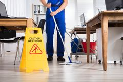 Janitor καθαρίζοντας πάτωμα στην αρχή Στοκ Φωτογραφίες