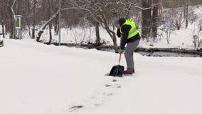 Janitor καθαρίζοντας πεζοδρόμιο από το χιόνι απόθεμα βίντεο