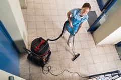 Janitor σκουπίζοντας με ηλεκτρική σκούπα πάτωμα Στοκ Εικόνες